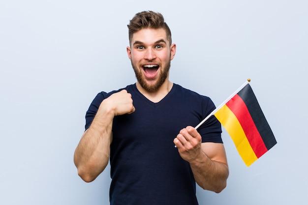 ドイツの旗を保持している若い白人男は、彼自身を指して驚いて、広く笑っています。