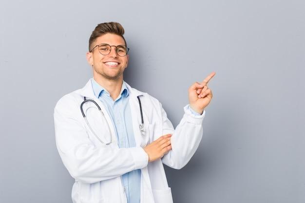 Молодая блондинка доктор человек улыбается весело указывая с указательным пальцем прочь.
