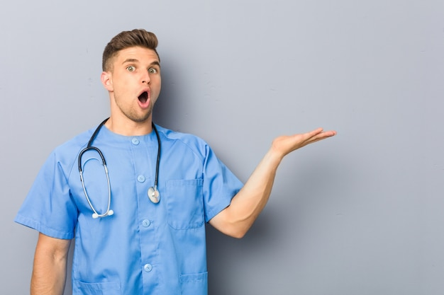 若い看護師の男は、手のひらにコピースペースを保持して感銘を受けました。