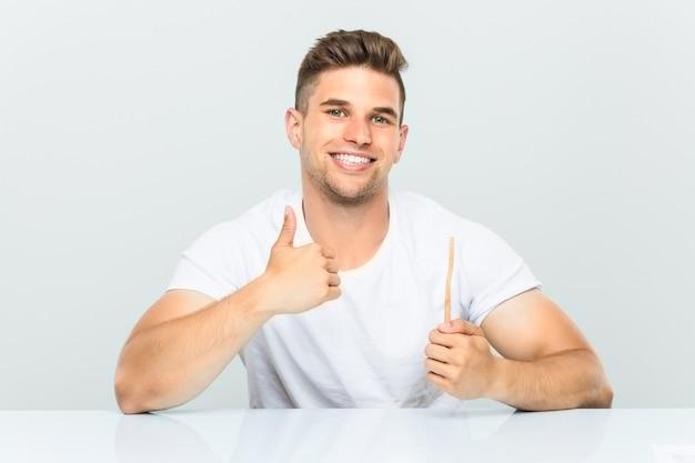 若い男笑顔と親指を上げる