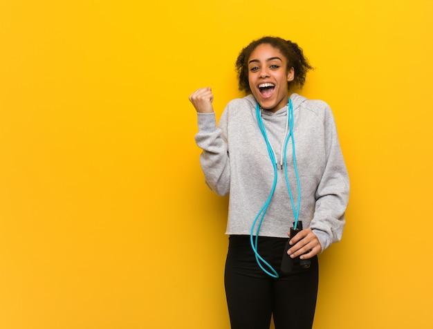Молодой фитнес черная женщина удивлена и шокирована. держа скакалку.