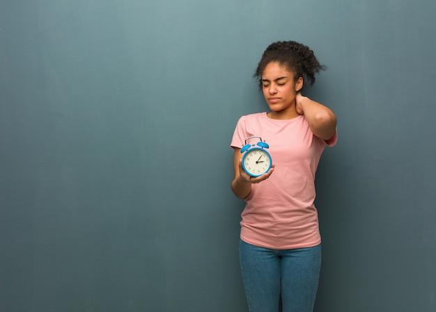Молодая негритянка страдает боль в шее. она держит будильник.