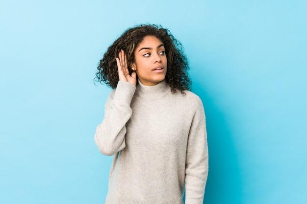 Молодая афро-американская женщина вьющиеся волосы пробуя слушать сплетню.