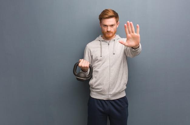 Молодой рыжий фитнес человек положить руку впереди. держа гантель.