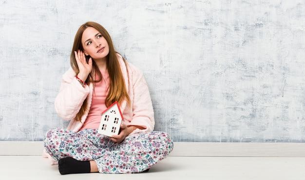 Молодая кавказская женщина держа значок дома пробуя слушать сплетню.