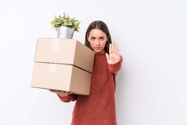 ボックスを保持している若いコーカサス地方の女性は、あなたを防ぐ差し出された一時停止の標識を示す手を伸ばして立っています。