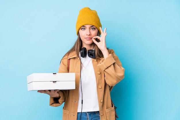 Молодая кавказская женщина держа пиццы изолированный с пальцами на губах держа секрет.