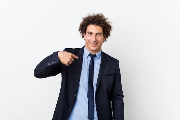 Молодой бизнес кудрявый человек против белой стены лица, указывая рукой на рубашку копирования пространство, гордый и уверенный