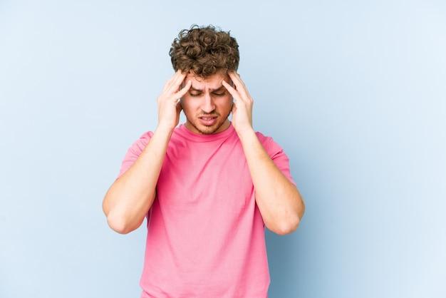 若いブロンドの巻き毛の白人男性は寺院に触れると頭痛を持っていることを分離しました。