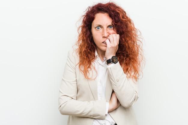 爪をかむ白い壁に対して分離された若い自然な赤毛ビジネス女性、神経質で非常に心配しています。