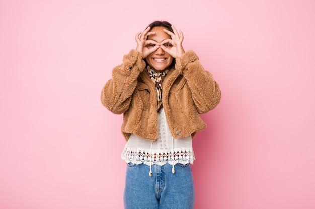 Молодая индийская женщина смешанной расы, одетая в короткую дубленку, показывает знак «хорошо» над глазами
