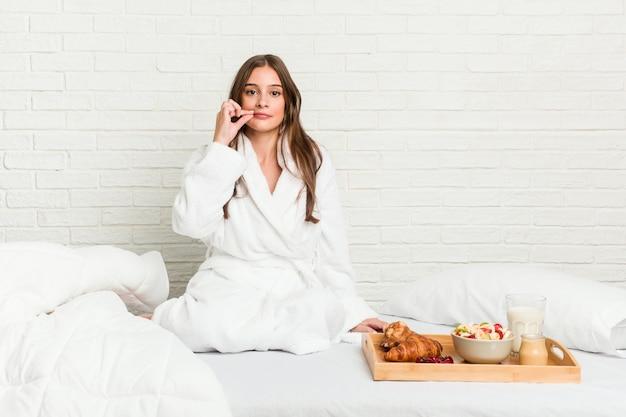 Молодая кавказская женщина на кровати с пальцами на губах держа в секрете.