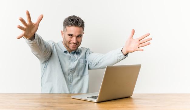 Молодой красивый человек, работающий с его ноутбуком чувствует себя уверенно, давая обнять камеру.
