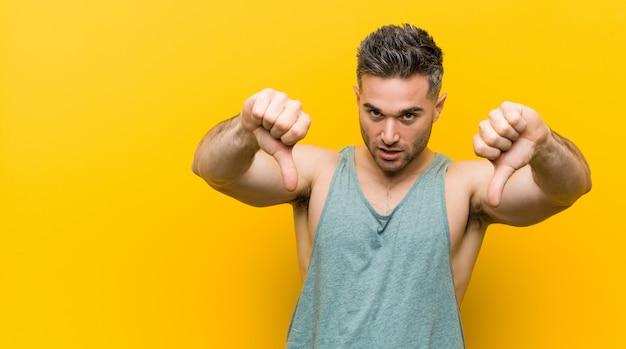 黄色の背景に対して親指を示すと嫌悪感を表現する若いフィットネス男。