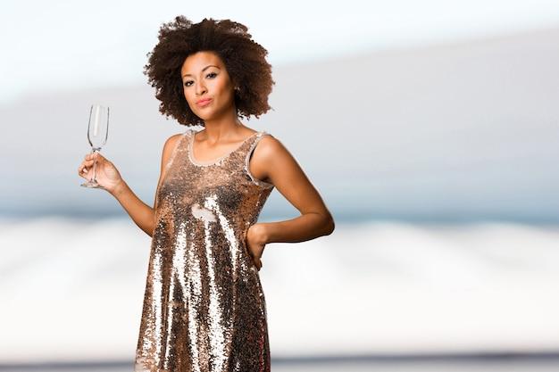 Молодая чернокожая женщина с коктейльным бокалом