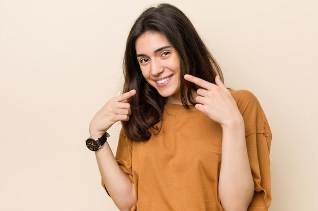 口に指を指して、ベージュ色の背景笑顔の若いブルネットの女性。