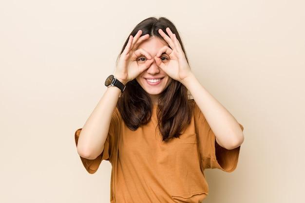 Молодая брюнетка женщина на бежевом фоне, показывая хорошо знаком над глазами