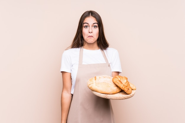 Молодая кавказская женщина хлебопека изолировала плечи плеч и открытые глаза смущенные.