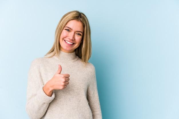笑顔と親指を上げる分離された若い金髪白人女性