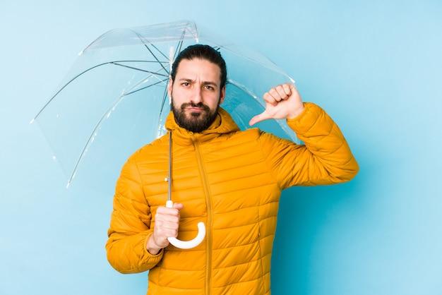 孤立した傘を保持している長い髪の外観を着ている若い男は、次の例のように誇りと自信を感じています。
