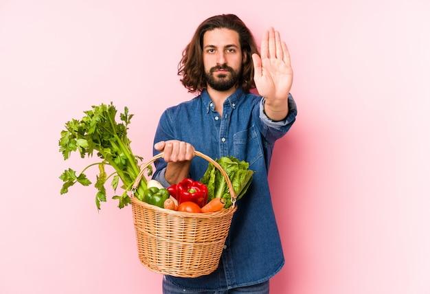 若い男が彼の庭から有機野菜を摘み、差し出された手で一時停止の標識を示す孤立した立って、あなたを防ぎます。