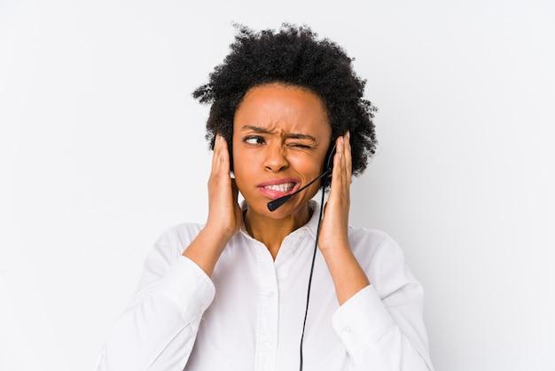 Молодая афро-американская женщина телемаркетера изолировала покрывать уши руками.