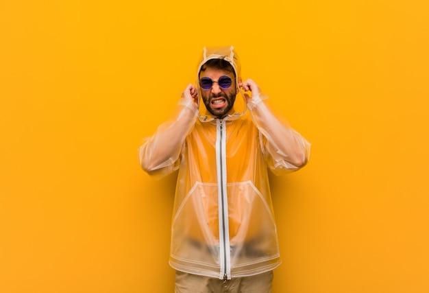 手で耳を覆うレインコートを着ている若い男