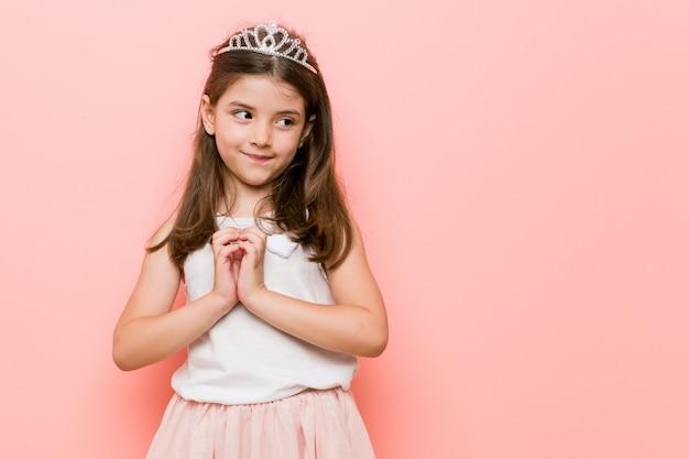 プリンセスルックを身に着けている女の子は、計画を考えて、アイデアを設定します。