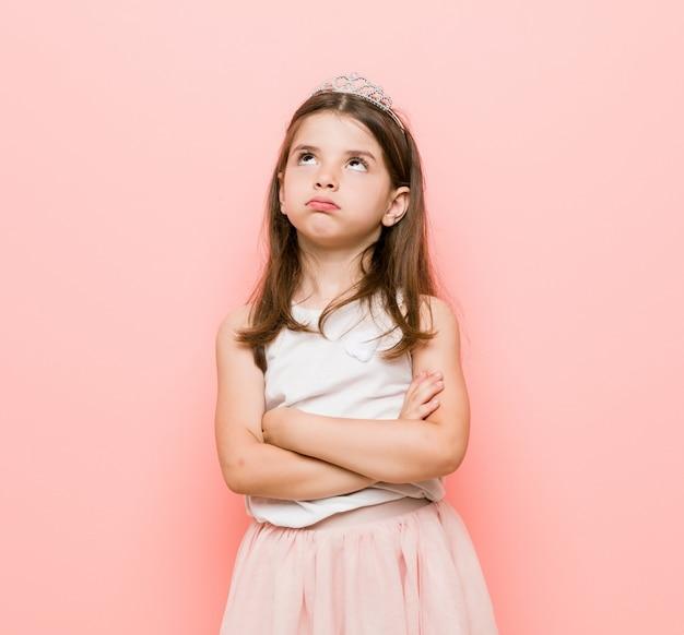 Маленькая девочка в принцессе выглядит уставшей от повторяющихся задач.
