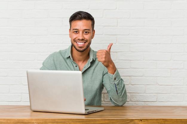 笑みを浮かべて、親指を上げる彼のラップトップで作業して座っている若いフィリピン人