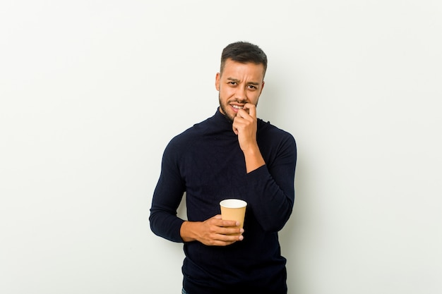 Человек молодой смешанной гонки азиатский держа ногти на вынос кофе сдерживая, слабонервный и очень тревоженый.