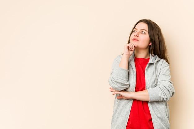 Молодая спортивная соблазнительная женщина смотрит в сторону с сомнительным и скептическим выражением.