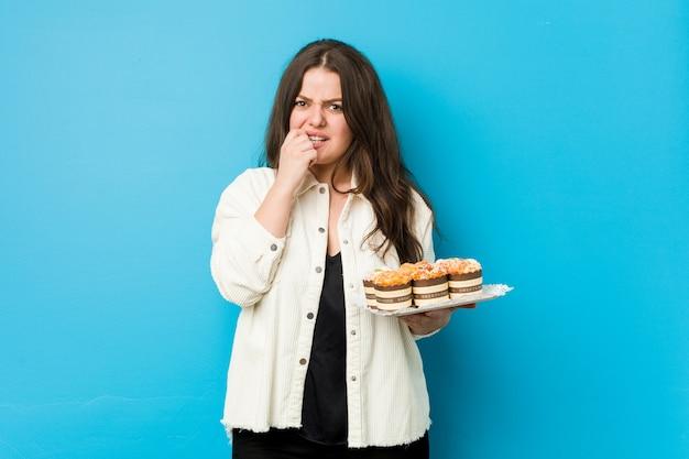 Молодая соблазнительная женщина, держащая кексы, кусающая ногти, нервная и очень взволнованная.