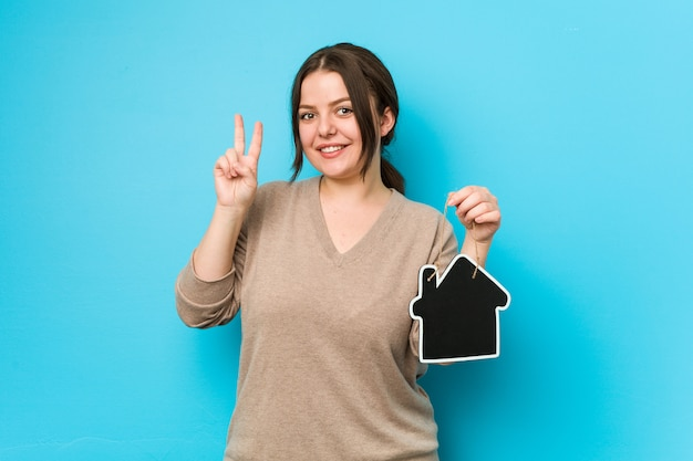 若いプラスサイズの曲線の女性が勝利のサインを示し、広く笑顔のホームアイコンを保持しています。