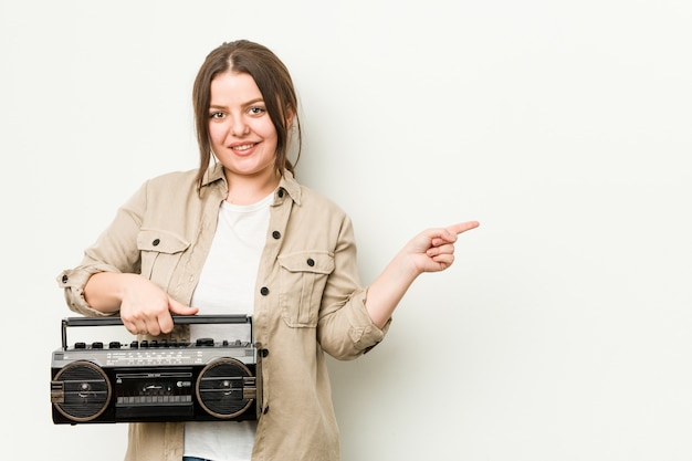 笑みを浮かべて、さておき、空白で何かを見せてレトロなラジオを保持している若い曲線の女性。
