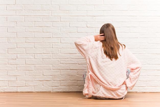 Молодая женщина в пижаме сзади думает о чем-то