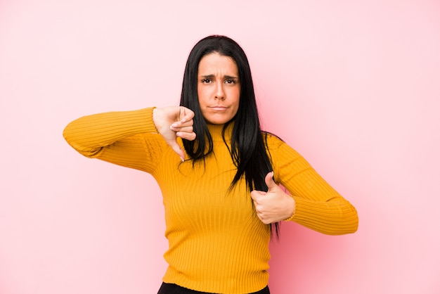 ピンクの背景に親指と親指を示す若い白人女性の分離の概念を選択するのは難しい