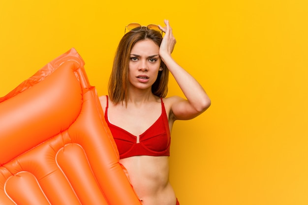 Молодая женщина в бикини, держа надувной матрас кровать в шоке, она вспомнила важную встречу.