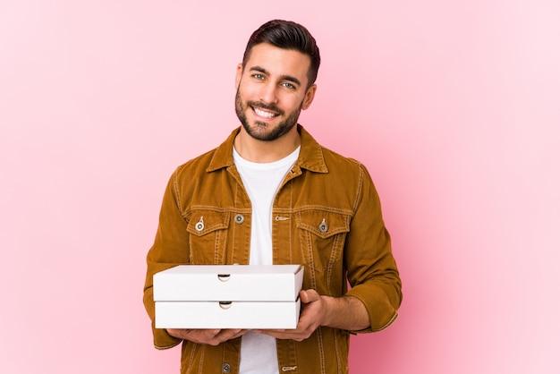 ピザを保持している若いハンサムな男は、幸せ、笑顔、陽気な分離しました。