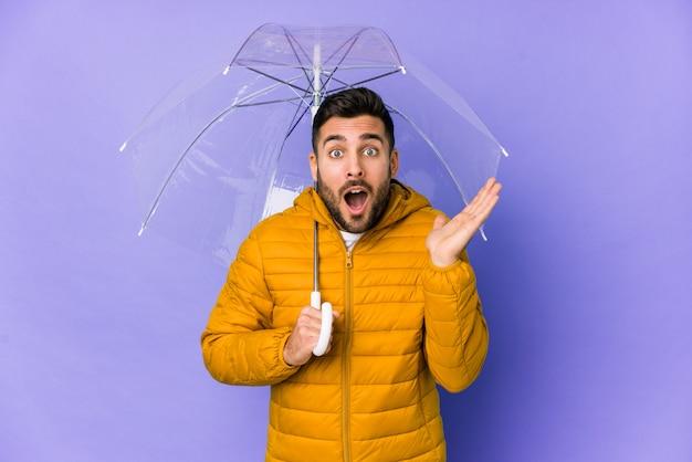 分離された傘を保持している若いハンサムな男は驚いてショックを受けた。