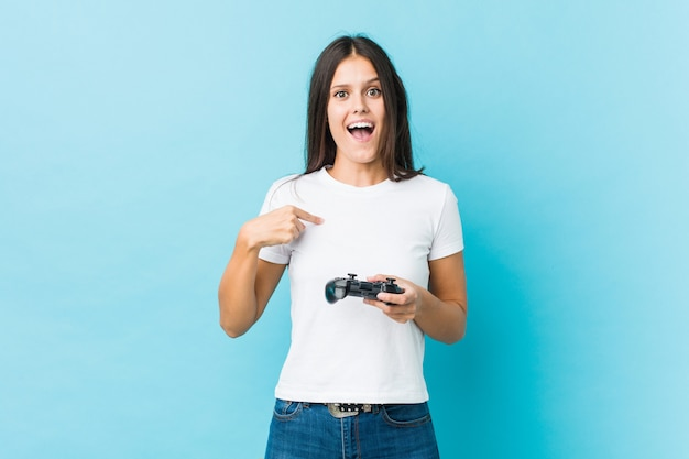 ゲームコントローラーを保持している若い白人女性は、自分自身を指して驚いて、広く笑っています。