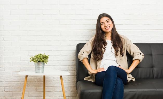 Молодая арабская женщина, сидя на диване, уверенно держа руки на бедрах.