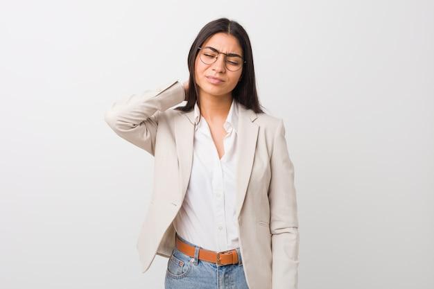 座りがちなライフスタイルのため首の痛みに苦しんでいる白い背景に対して隔離される若いビジネスアラブ女性。