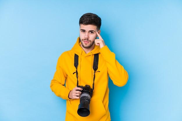 若い白人の写真家の男は、指で指差し、思考、タスクに焦点を当てて分離しました。