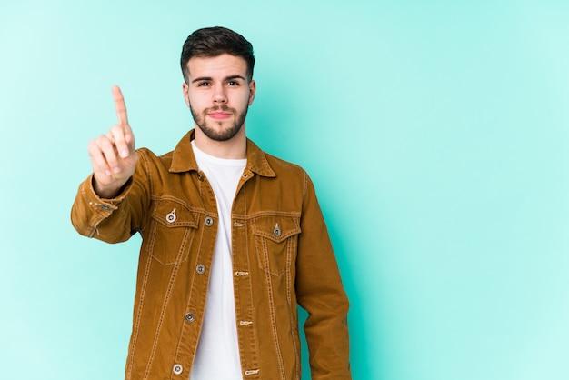 指でナンバーワンを示す若いハンサムな男。