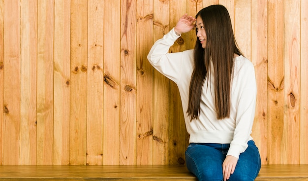 額に手をつけて遠くを見ている木製の場所に座っている若い中国人女性。