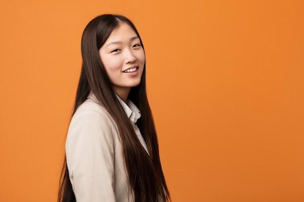 Молодой бизнес китаянка смотрит в сторону, улыбаясь, веселый и приятный.