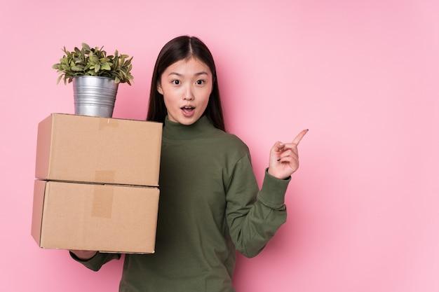 側を指している分離されたボックスを保持している若い中国人女性