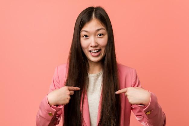 ピンクのスーツを着た若いビジネス中国人女性は、自分自身を指して驚いて、広く笑っています。