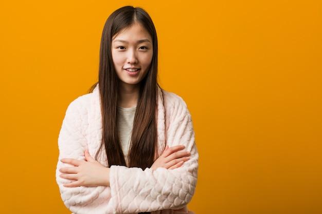 Молодая китайская женщина в пижаме, которая чувствует себя уверенно, скрещивая руки с решимостью.